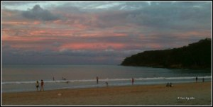 As the sun sets over Noosa Main Beach, people linger.