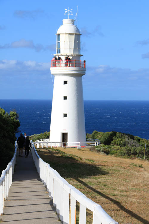 Image of a white lighthouse on the edge of a cliff with the blue ocean behind and pathway leading to the lighthouse ntrance