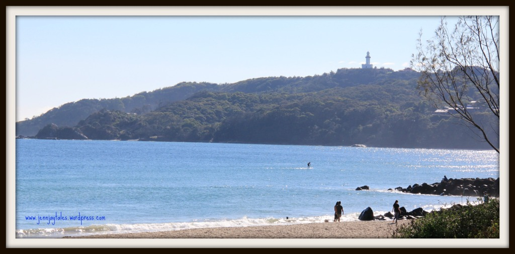 Image of sandy beach and ocean cliffs in the background with a lighthouse