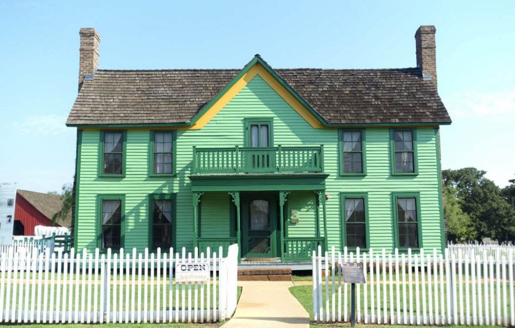 Renovated old style American farmhouse built green in colour with two chimneys