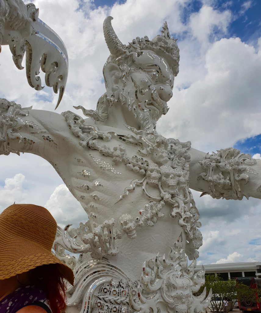 white sculpture of a mythical creature is decorated with mirror tiles
