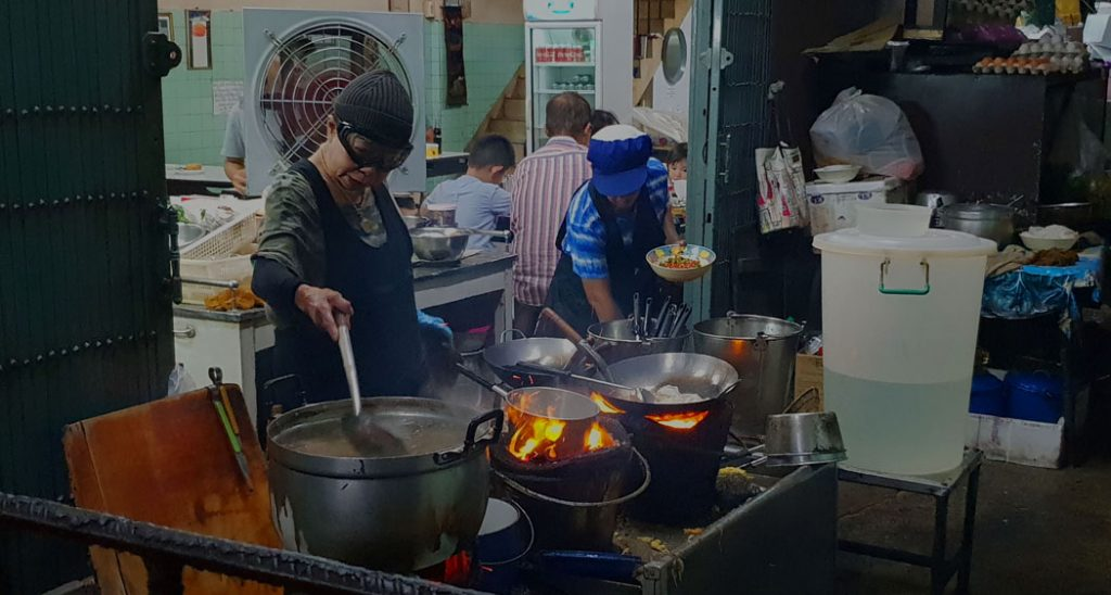 Image of an older woman wearing ski goggles as she cooks over a few saucepans and a wok
