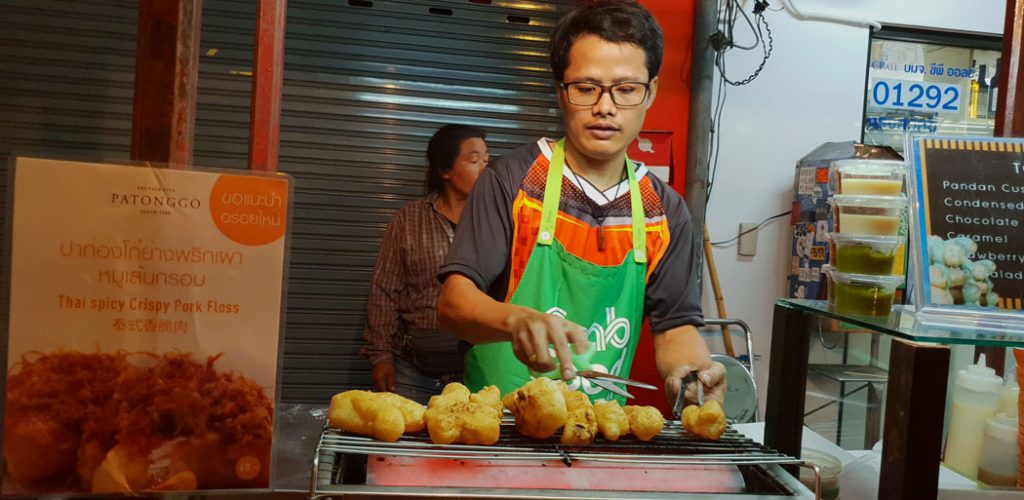 Image of a man standing over a deep fryer cooking pastries