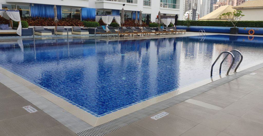 Image of a swimming pool with cabana slounges beside the pool
