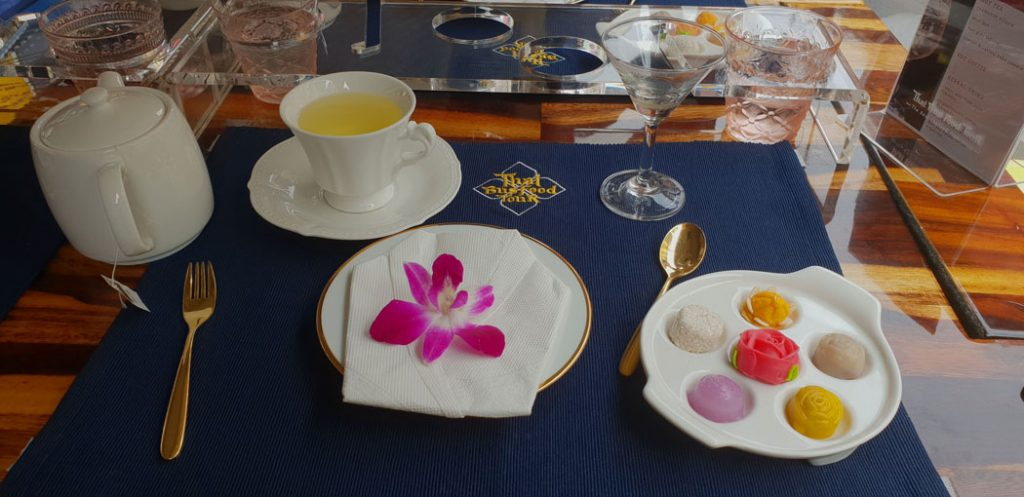 Image of a table set with a blue placemat and two plates one with a purple orchid the other with small flowers and