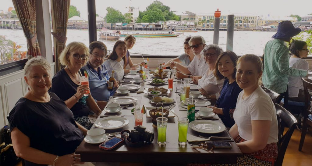 Image of a long table with ten diners sitting on opposite side. There is a view of a river from the window near the table and a few Thai boats floating on the river
