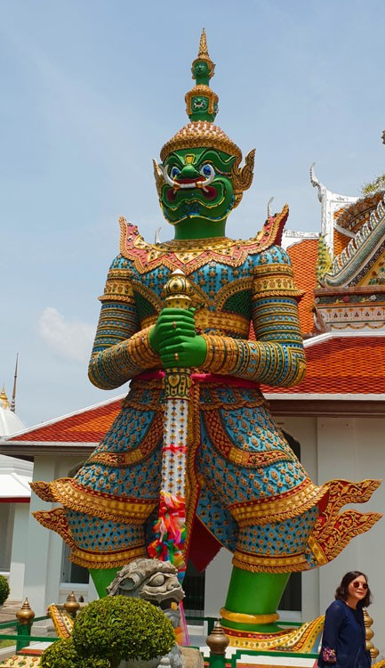 Image of a giant statue with green face and bright colours of blue and green a gold