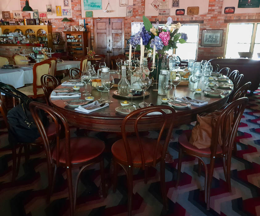 Image of an antique table set with dinner plates and wine glasses and a bunch of hydrange flowers in the center