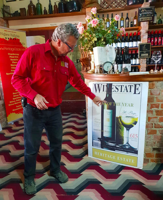 Image of a man in red shirt and dark trousers pointing to a large poster attached to a bar. The poster is of a bottle of wine next to a glass filled with wine
