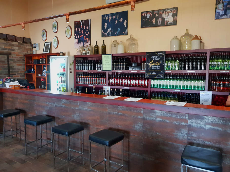 Image of a bar with bar stools and shelves filled with bottles of wine and family portraits on the wall above the shelves