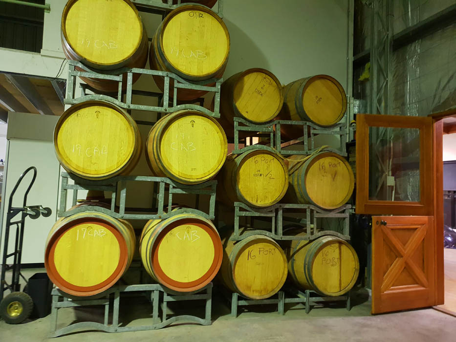Images of the backroom of a wine cellar with large wine barrels stacked on shelving