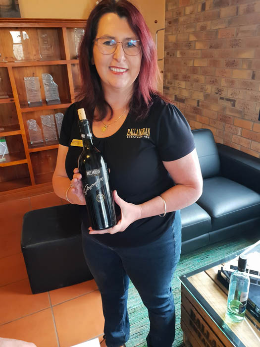 Image of a smiling woman wearing blue jeans and black tshirt holding a corked bottle of wine