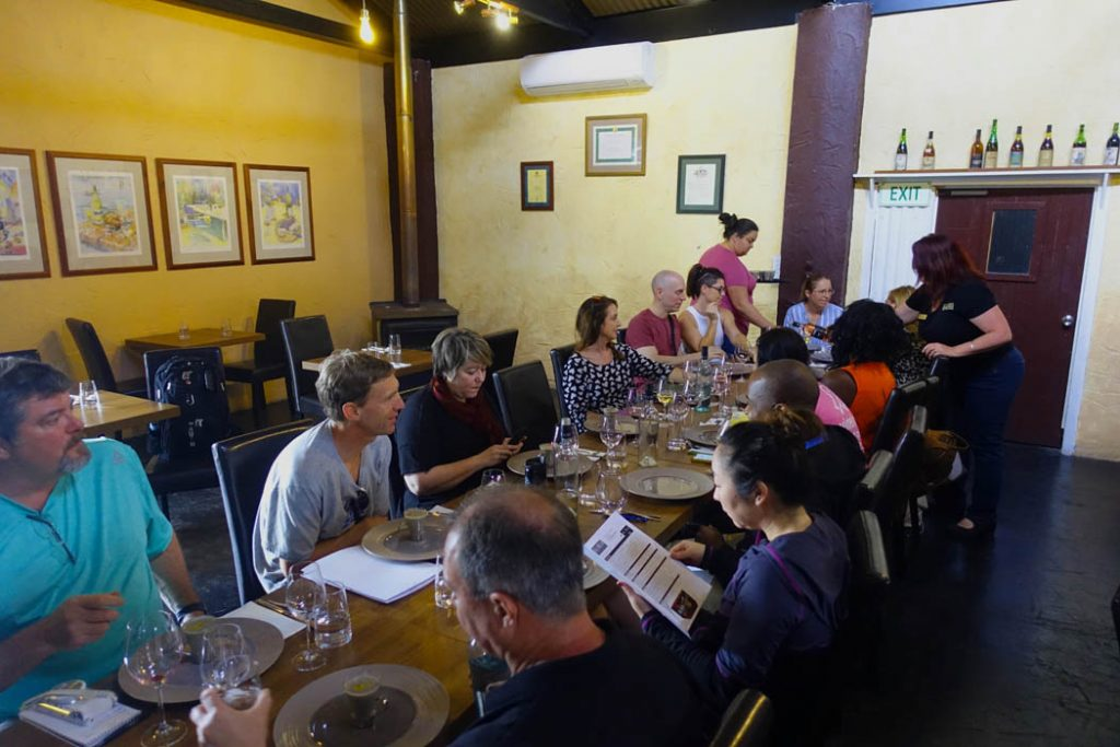Image of a large long rectangular shaped table with people seated around the table eating lunch and drinking wine