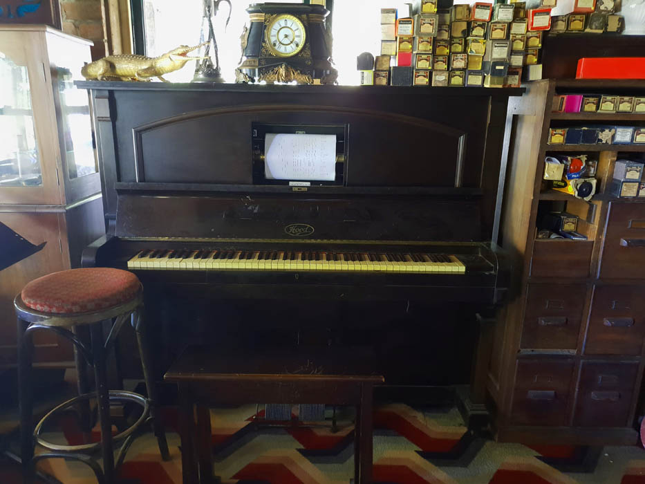 Image of a pianola and seat on top of the pianola is a vintage carriage clock