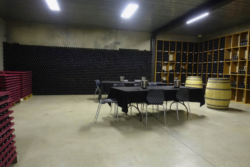 Image of an undergound cellar with rows of wine bottles aginst the walls and a two tabels with chairs
