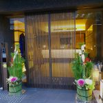 Screen door leading into a hotel reception with potted plants on either side of the entrance