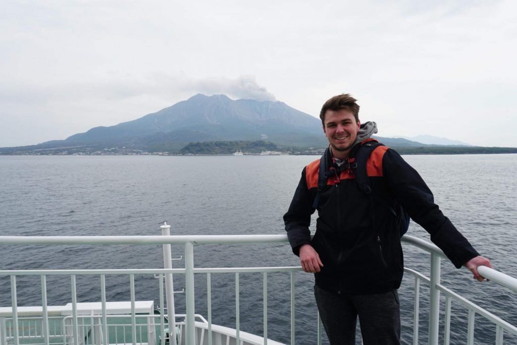 Young man stands on a platform leaning against a fence with an active volcano behind him in the distance