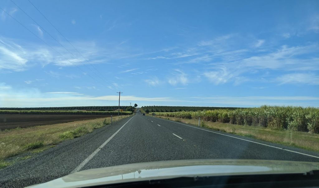 Open bitumen road with sugarcane and farm paddocks on eitehr side