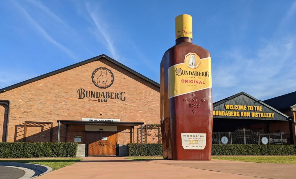 Large bottle of Bundaberg Rum outside the building with sign saying Bundaberg Rum Distillery