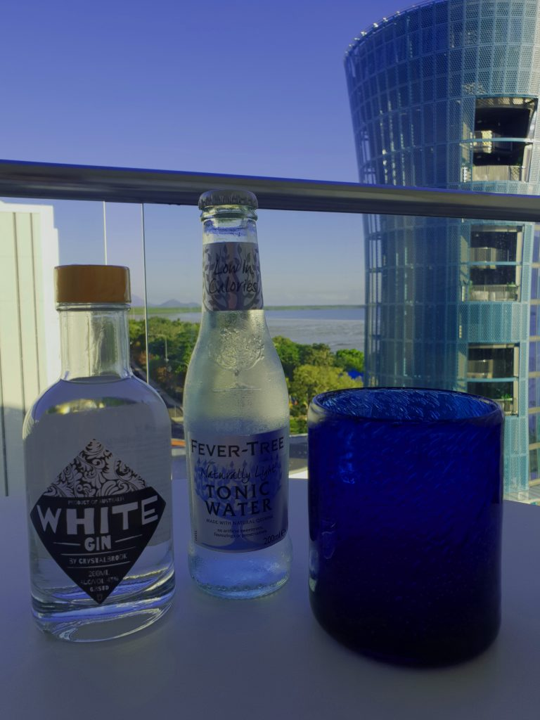 Bottle of gin a bottle of tonic and a blue glass on a table