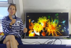 Woman sitting with a microphone next to a TV with an image of coral on the screen