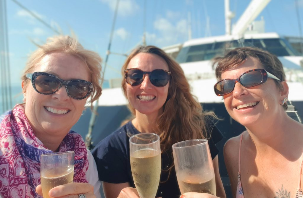 Three women are standing closely together on a boat holding plastic flutes filled with sparkling winechamp