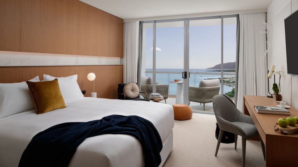 Hotel room showing a queen sized bed chair and desk sliding glass doors showing view to the ocean
