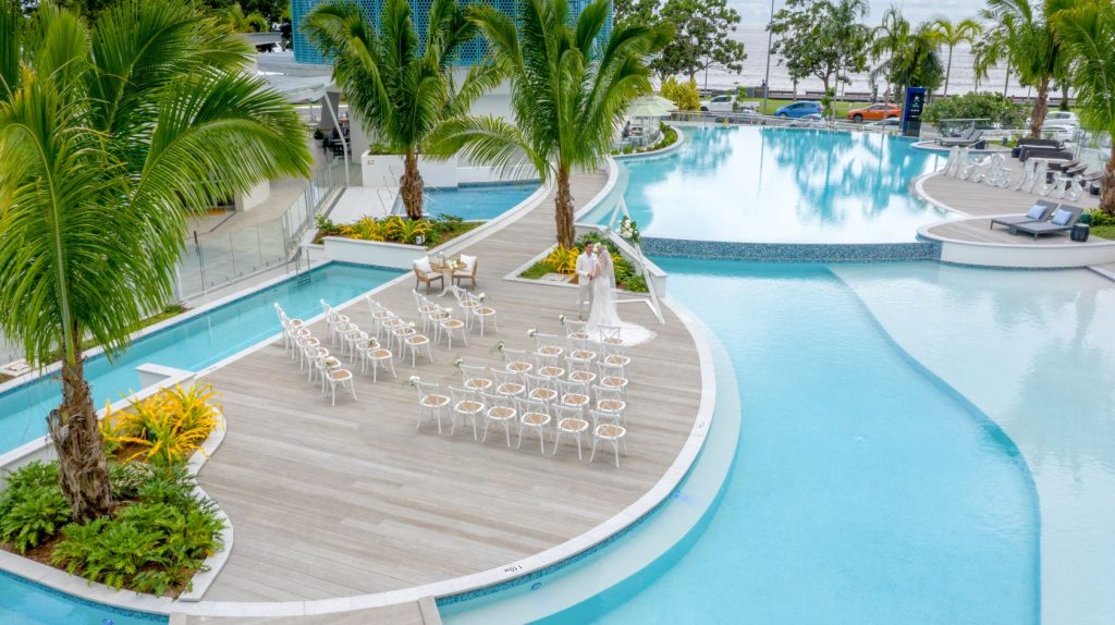 Oblong shaped hotel pool with deck in the centre and palm trees on the decking