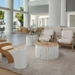 Two white chairs and small table in a open plan hotel lobby