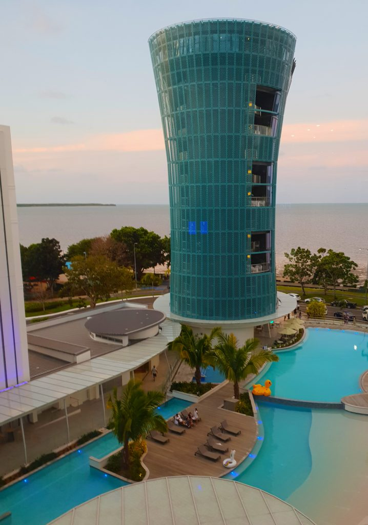 A 12 storey tower overlooking a hotel pool with ocean in the background