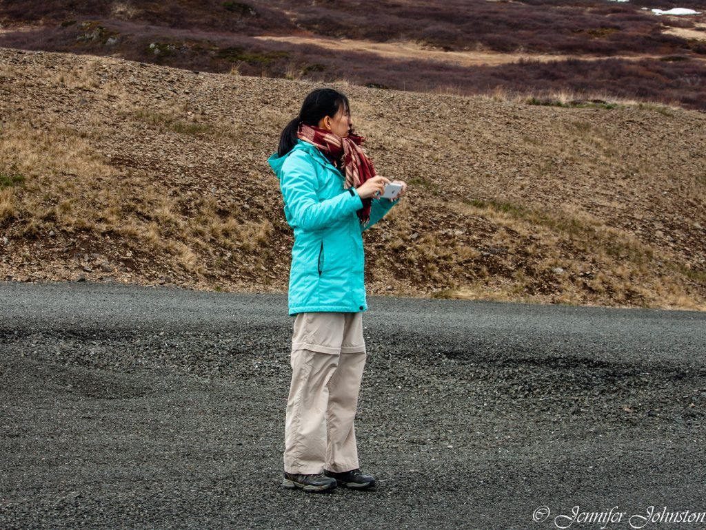 Woman in bright blue jacket and cream trousers stands in the middle of an open road with phone in hand ready to take a picture