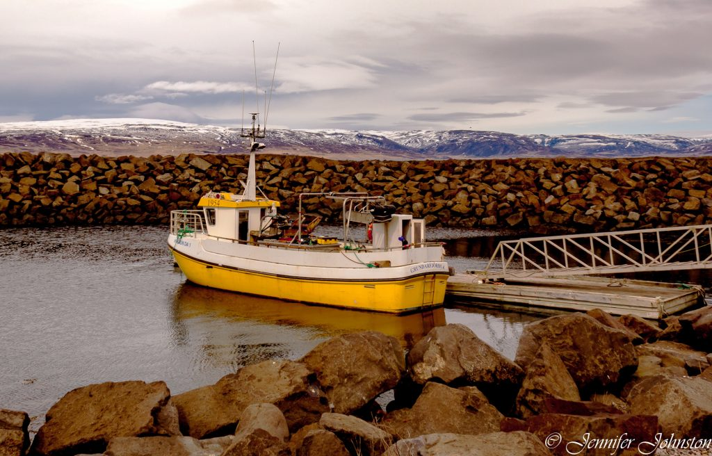 Yellow and white fishing boat moored near a jetty mountains in the background