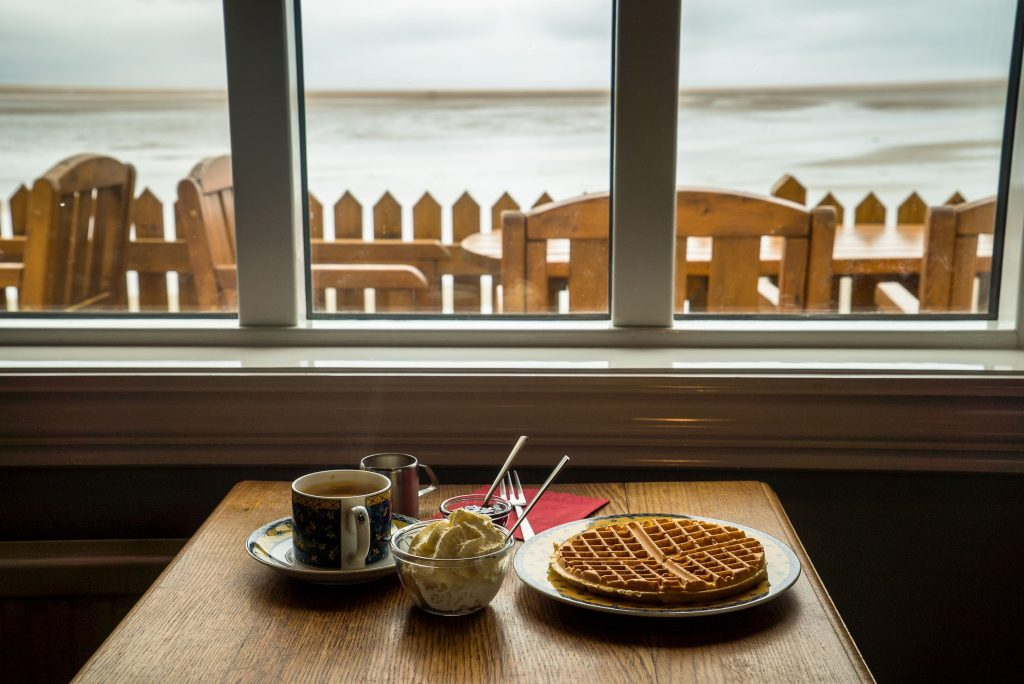 Small dining table near a window overlooking the water with coffee cup and waffle on a plate
