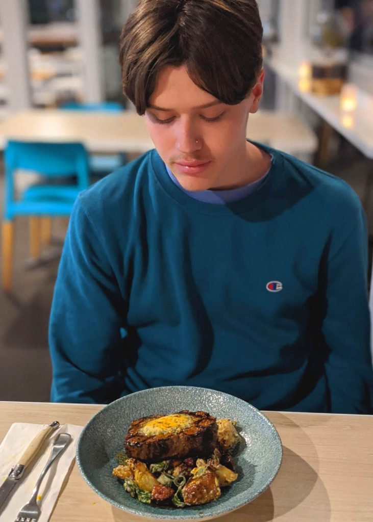 Teenager in blue shirt looks down at a plate of food on the table