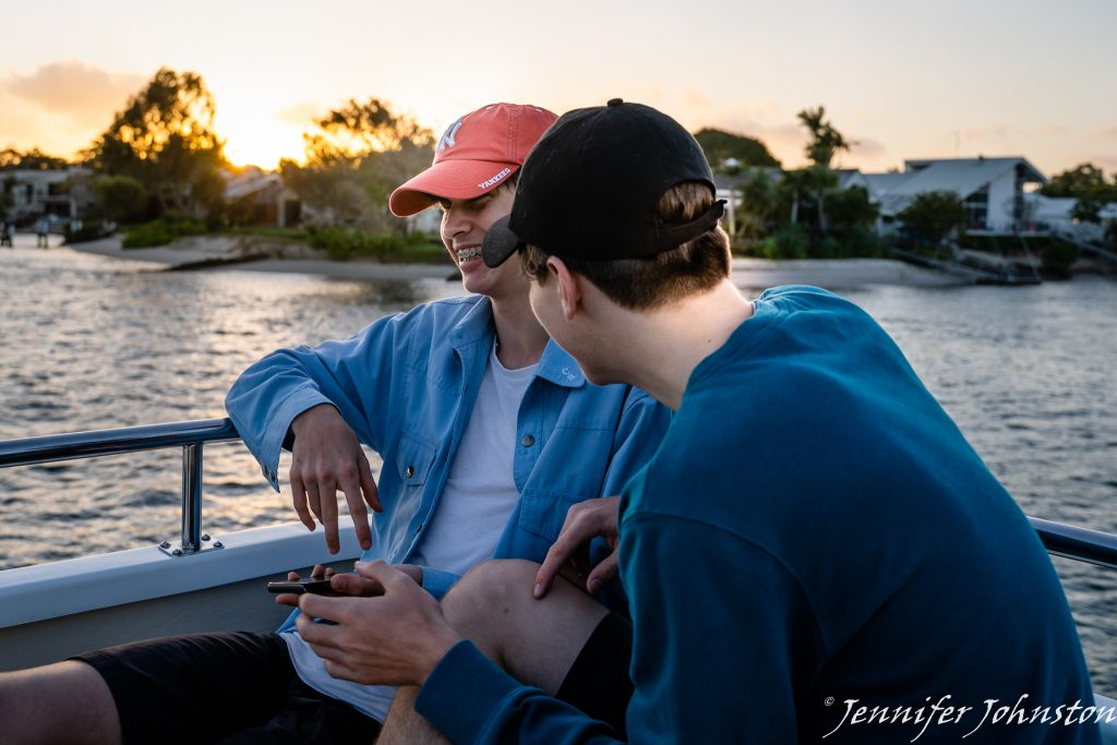 Two teenage boys sitting together on a boat