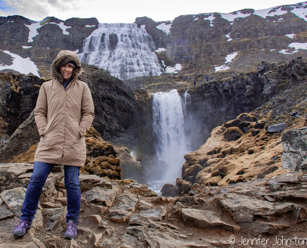 Woman in brown jacket and blue jeans stands on a rocky outcrop in front of a large waterfall