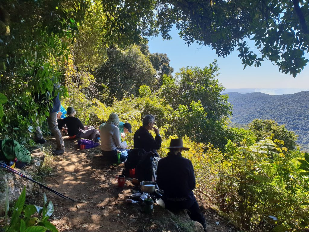 Group of people sitting down having a cup of tea on the side of a mountain