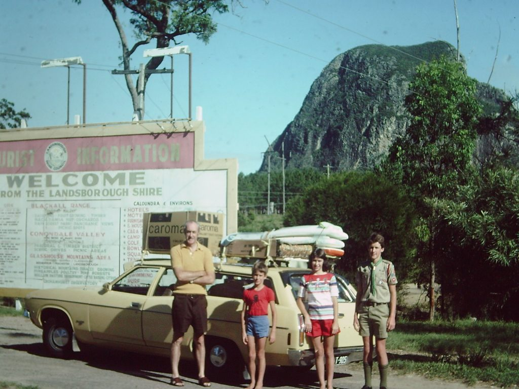 Old family photo showing three kids and a father standing in front of a family station wagon car with loaded roof racks