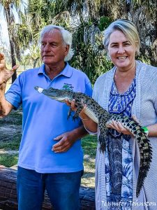 An older man wearing blue shirt stands next to woman wearing dress and cardigan who is holding a baby crocodile
