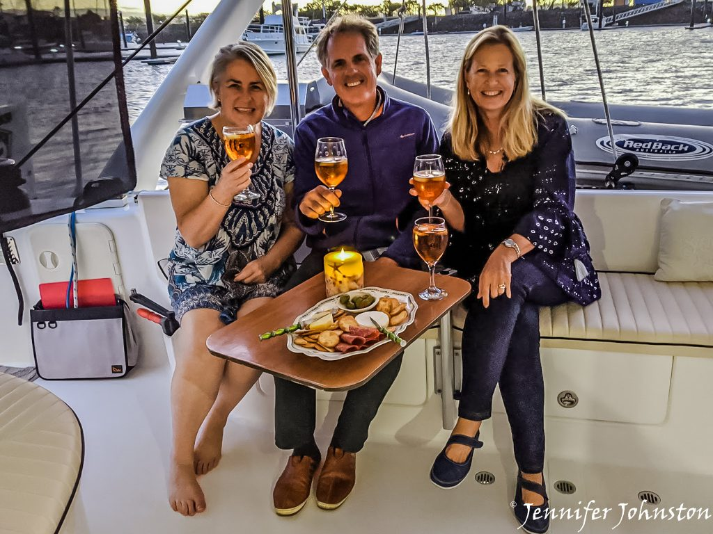 Three people each holding a glass of wine sitting togther on the lounge of a yacht