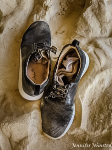 Pair of black shoes with socks inside on sandy beach