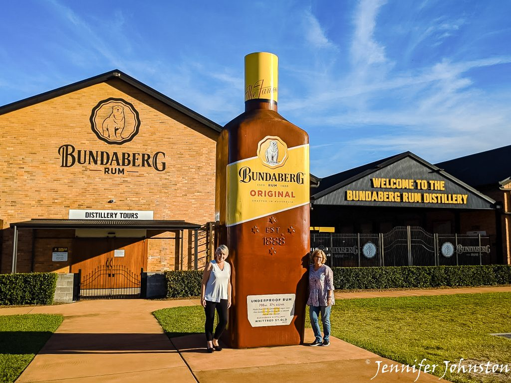 Two women stand on either side of an oversized replica bottle of Bundaberg Rum