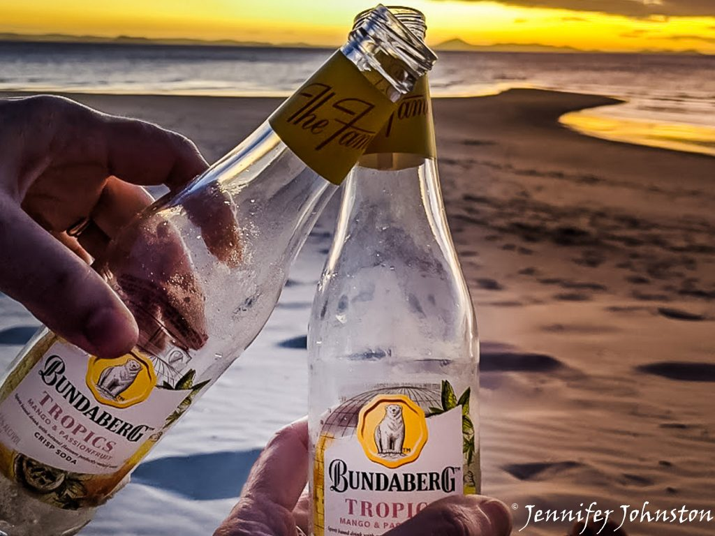 Two glass bottles of flavoured drink held in a hand with the sunset in the background
