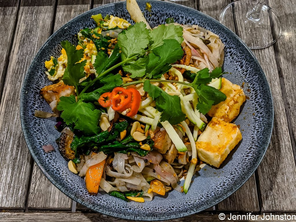 Picture of a plate with food on it - bright coloured vegetables and green leaves