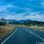 Picture of an open bitumen road with mountains in the background