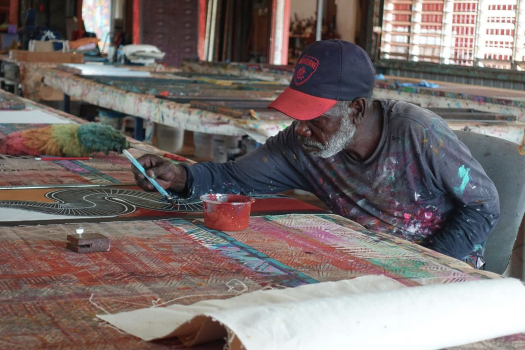 Image showing a seated Indigenous artist wearing a black and red baseball cap and pinat splattered t-shirt leaning over a canvas with a painbrush in hand