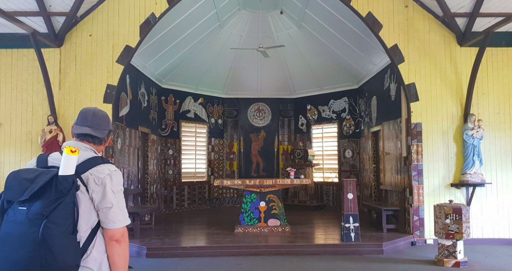 Image showing the brightly painted altar of a wooden church the walls are covered with images of animals painted by Australian Indigenous artists