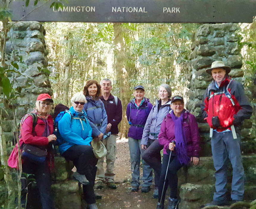 Image of a group of eight bushwalkers standing under a sign that says Lamington National Park