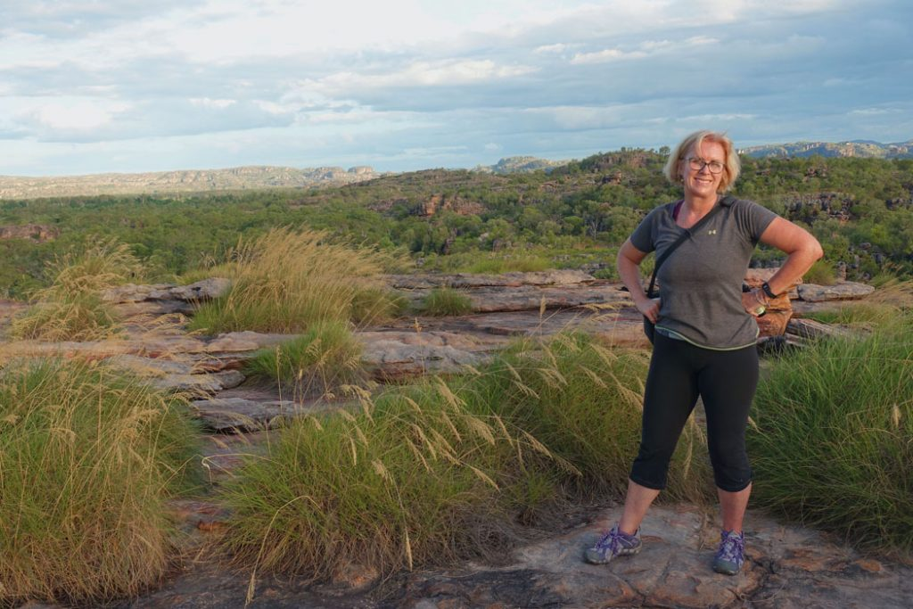 Image of a woman in a gery tshirt and black yoga pants and purple and gray running shoes standing on top of a rock formation background of more rock formations
