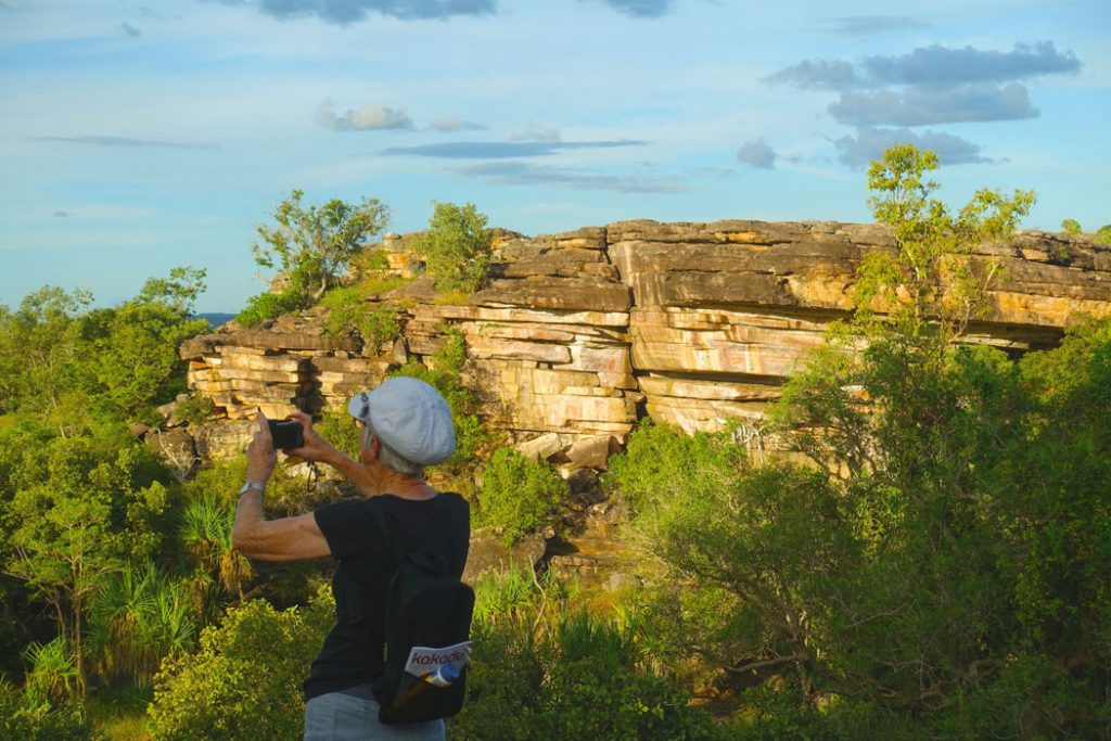 Image of teh back of a woman standing she is wearing a white hat black tshirt and jeans and is holding up a camera taking a photo of the scenery in front of her